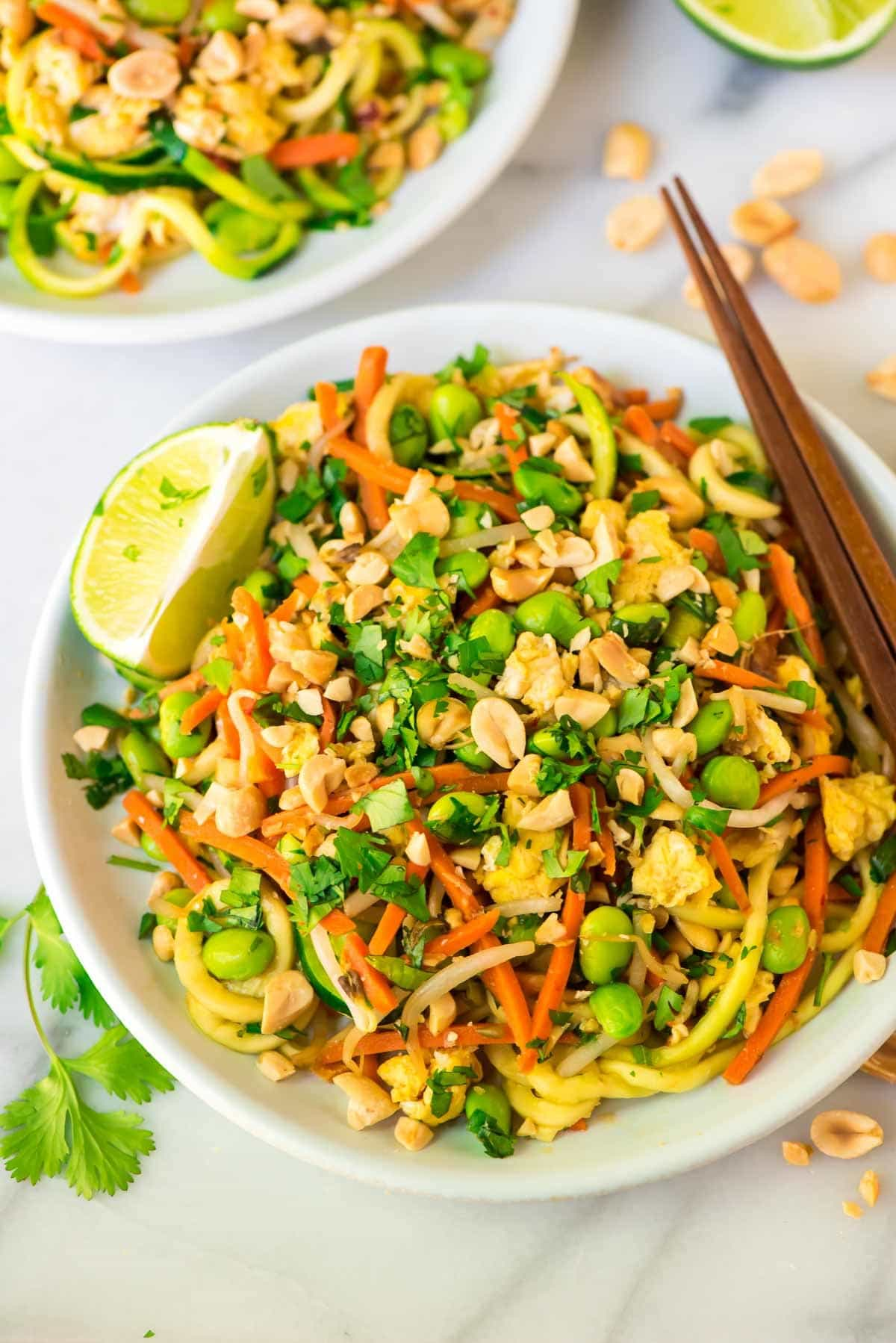 Easy Vegetarian Pad Thai with Zoodles in a white bowl with chopsticks and garnished with lime wedges, cilantro and peanuts
