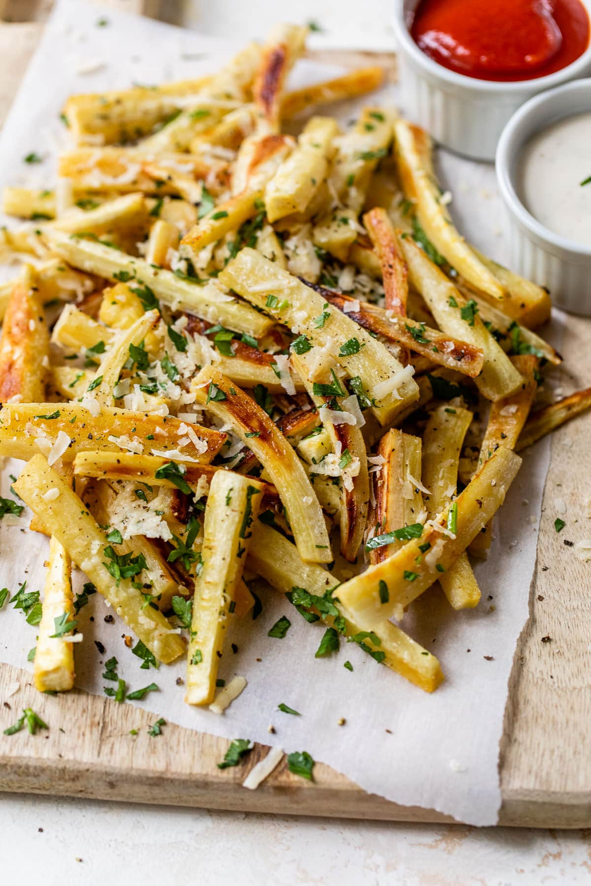Baked Parsnip Fries with Parsley and Parmesan on a sheet of parchment paper