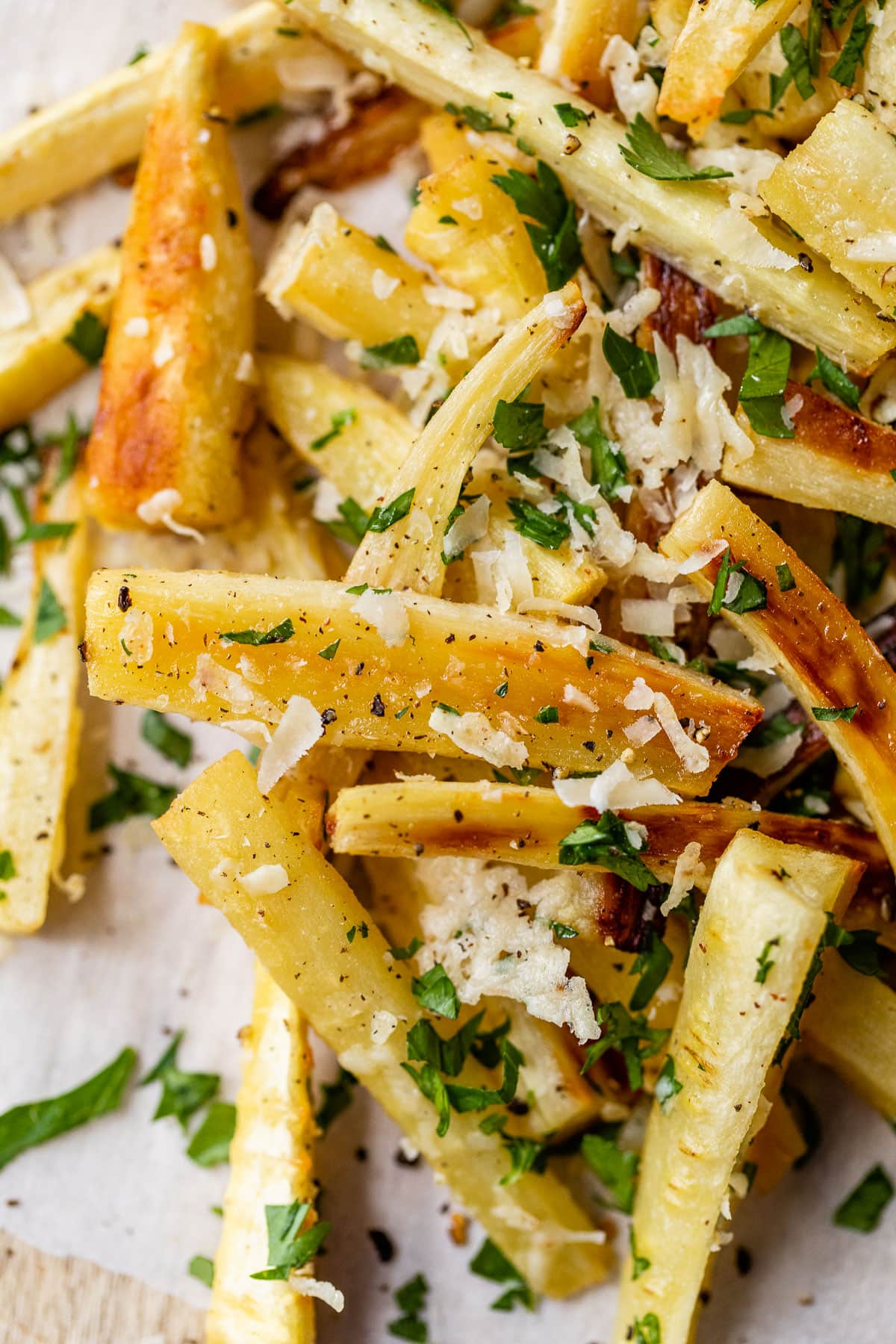 Parsnip Fries baked in the oven on a sheet of parchment paper garnished with parmesan and herbs