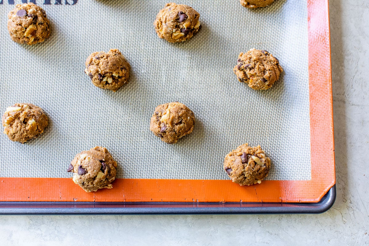 chewy chocolate chip walnut cookie dough scooped on a baking sheet