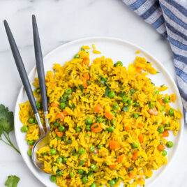 Simple turmeric rice on a plate with two spoons