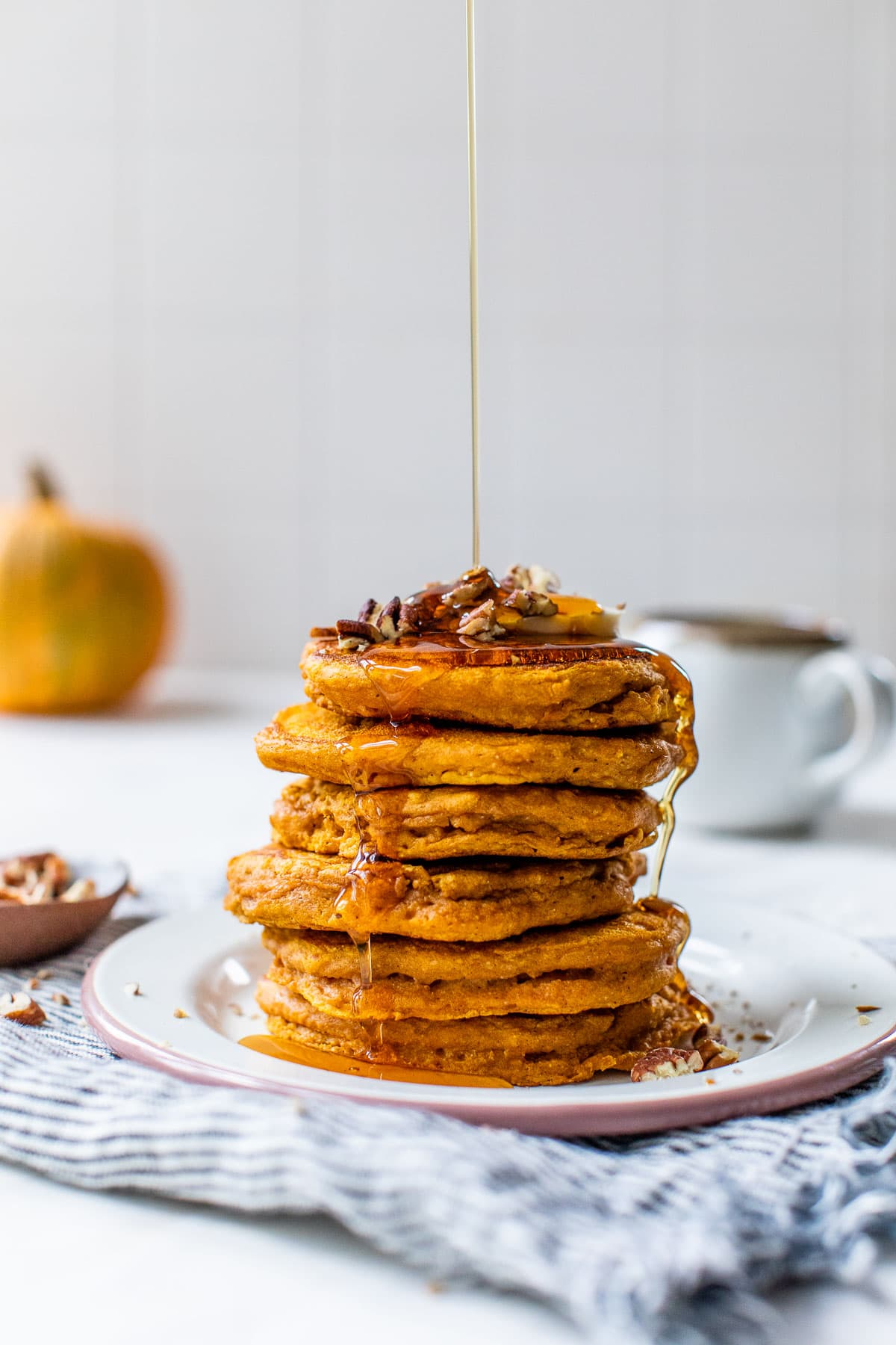 A stack of healthy pumpkin pancakes with syrup