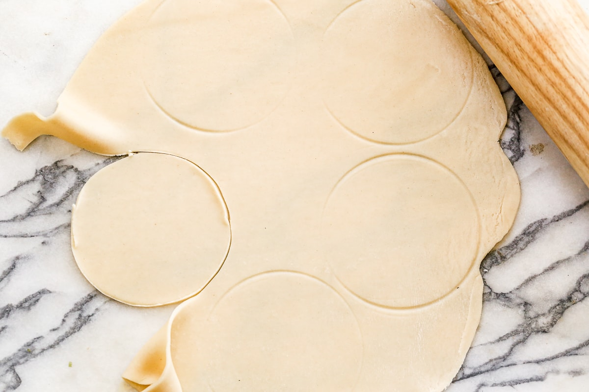 pie crust rolled out on a marble surface with circles cut out
