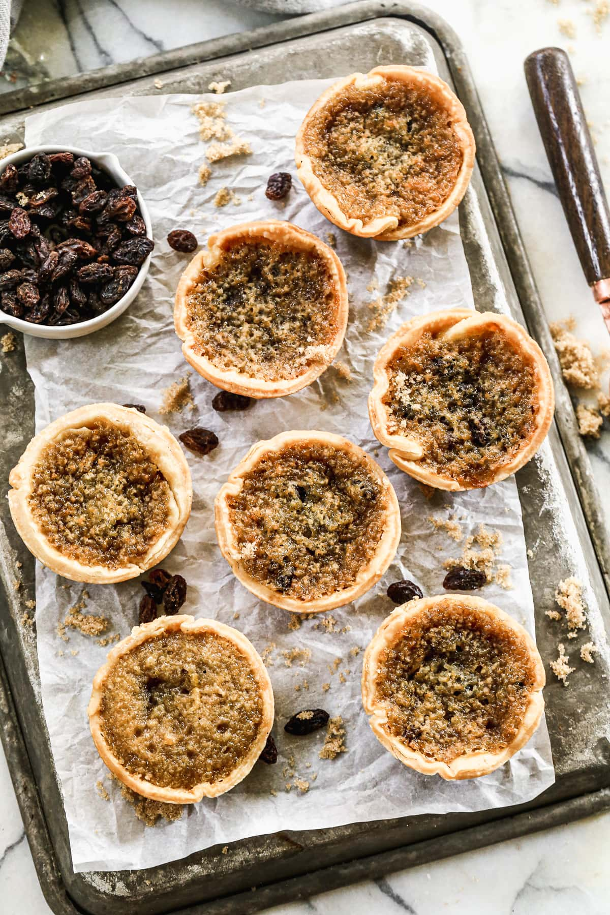 Mini Butter Tarts on a sheet pan with parchment paper, raisins, and brown sugar