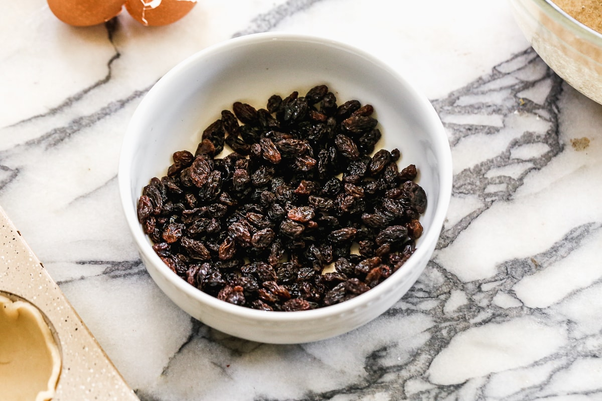 raisins in a white bowl with bourbon on a marble surface