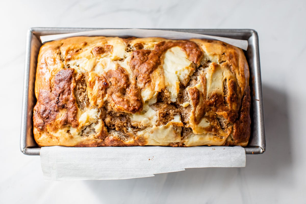 freshly baked cream cheese banana bread in a loaf pan with parchment paper