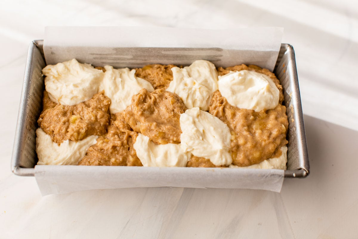 banana bread batter in a loaf pan with dollops of cream cheese filling on top ready to bake