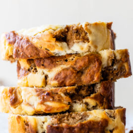 moist cream cheese banana bread with swirls in a stack of slices