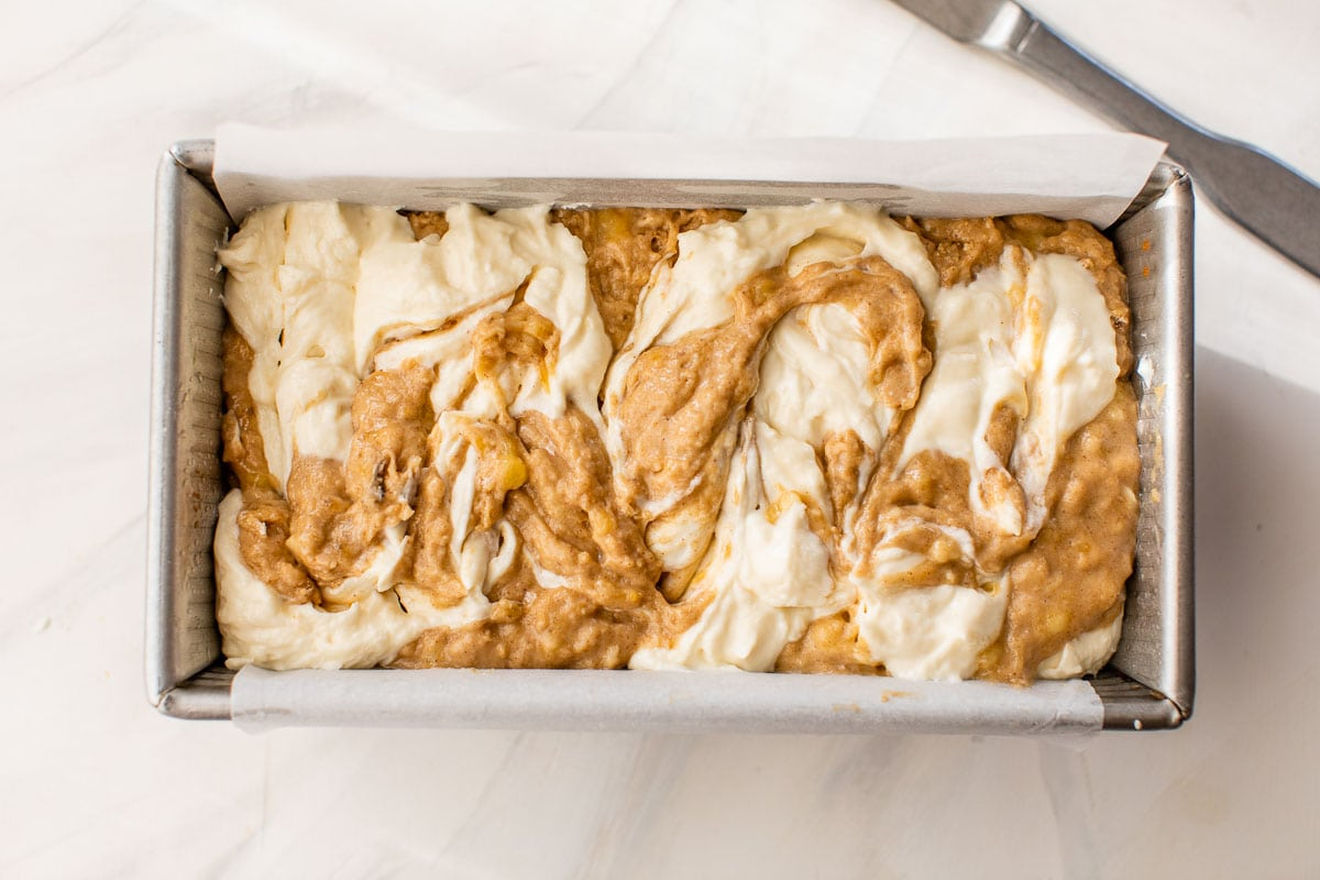 cream cheese filling and banana bread batter swirled together in a loaf pan before baking