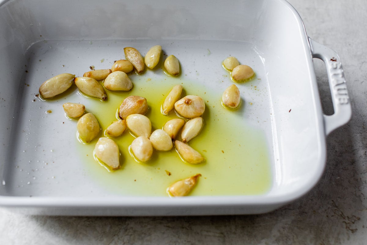 whole cloves of roasted garlic in a baking dish with olive oil