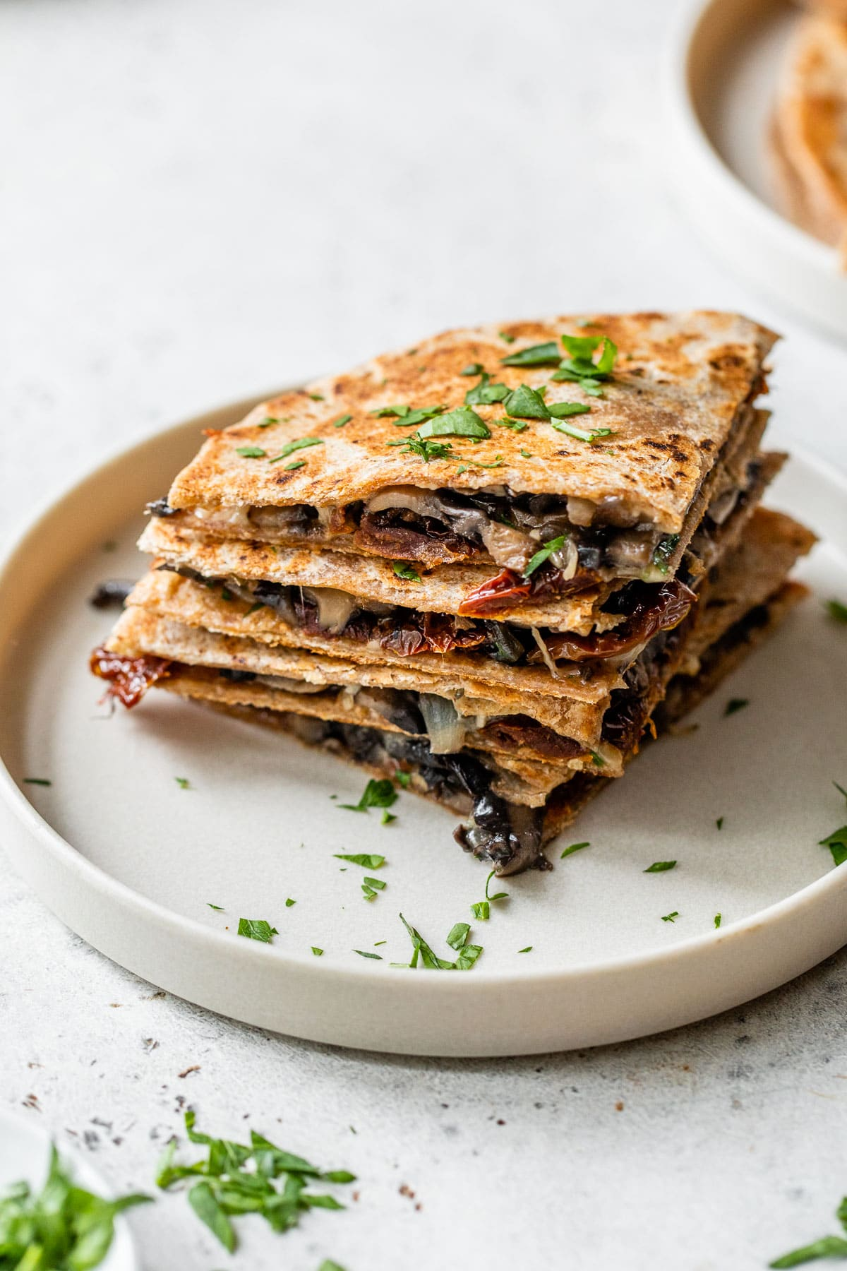 a stack of quesadillas wedges on a plate filled with mushrooms, cheese and tomatoes.