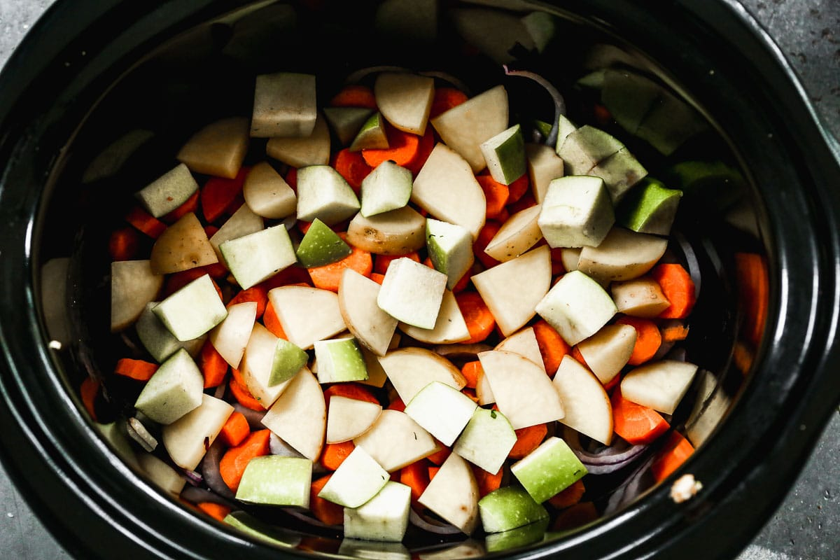 Cut apples, carrots, and potatoes s in a slow cooker