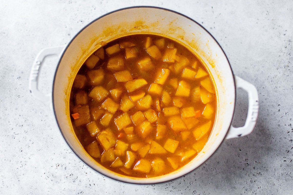 simmering vegan curried carrot soup in a soup pot
